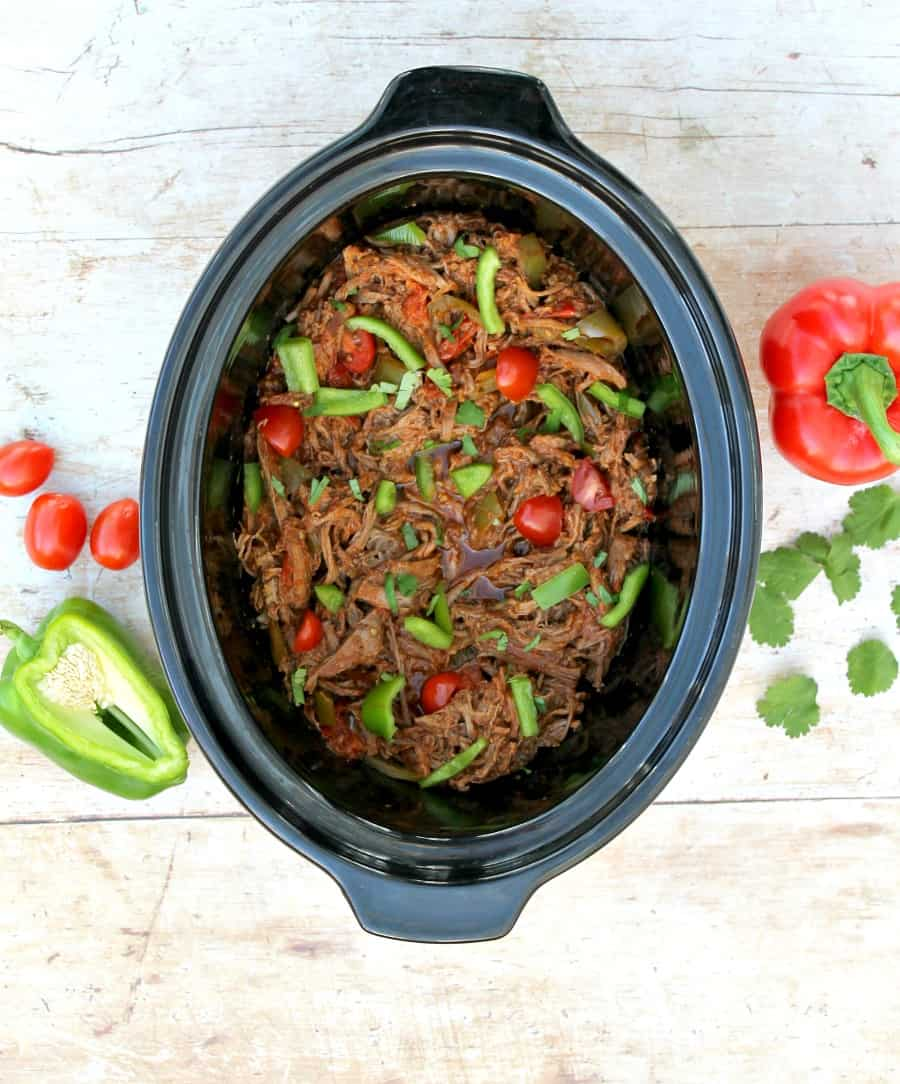View from above of slow cooker containing shredded beef and peppers on the table next to it.