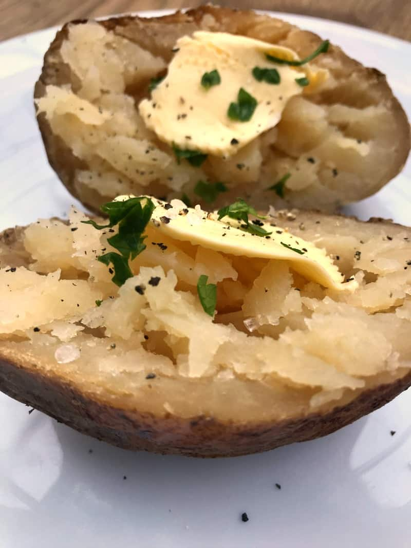 A baked potato cooked in the slow cooker, plain with butter
