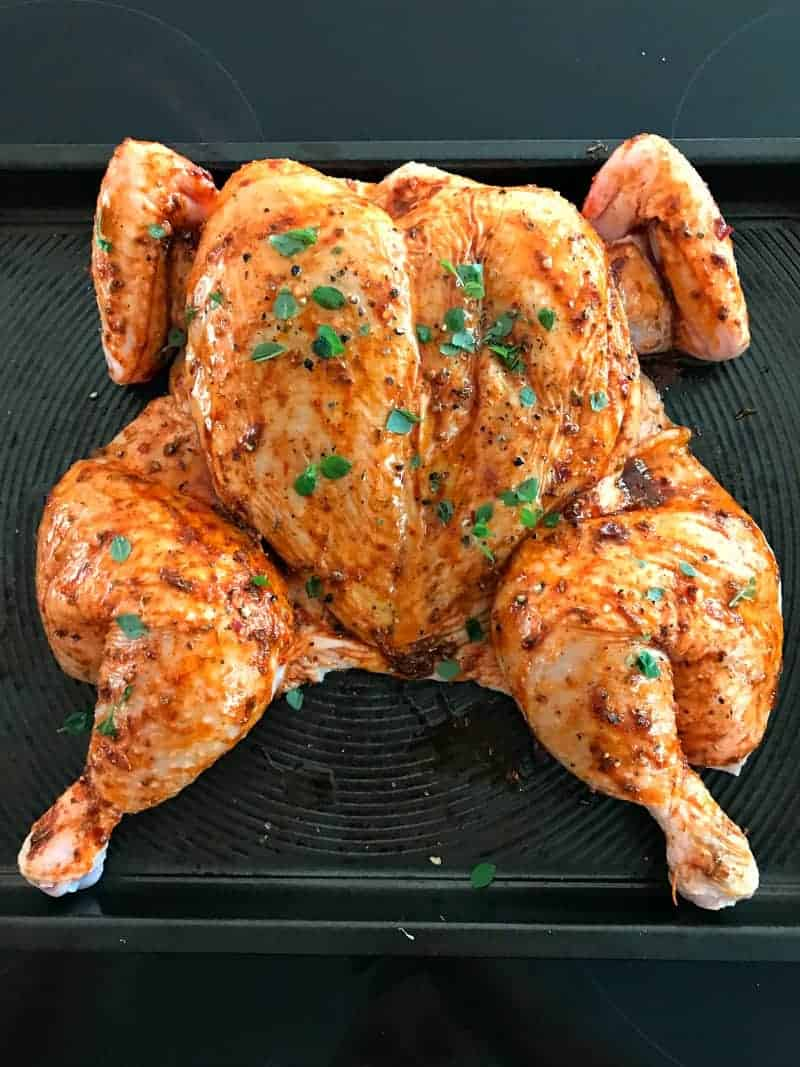 A chicken with a spice rub on an oven tray.