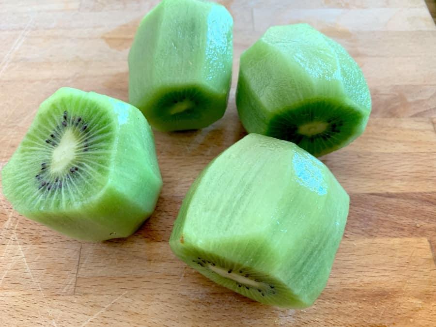 Peeled kiwi fruit on a board.