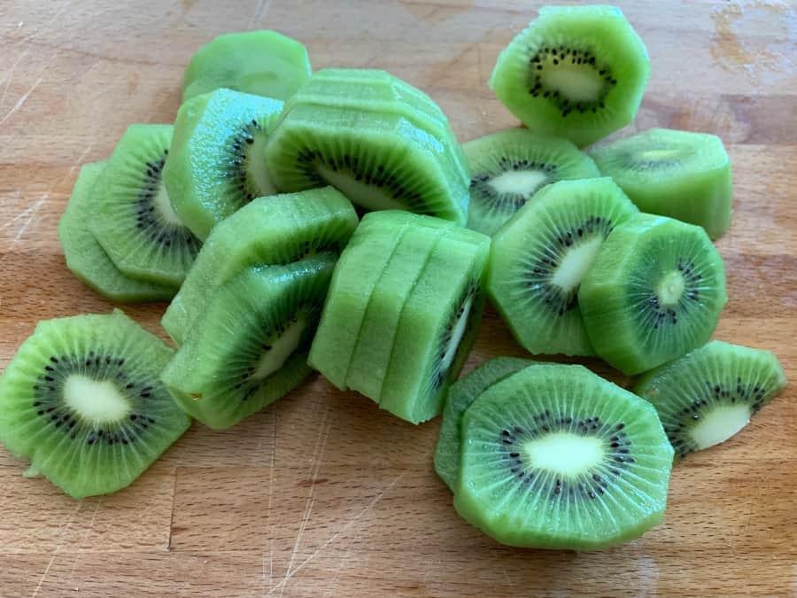 Sliced kiwi fruit on a chopping board.