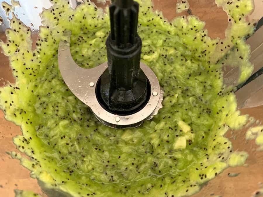 Pureed kiwi fruit in blender bowl after blending.