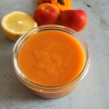Bowl of apricot curd with lemon and apricots.