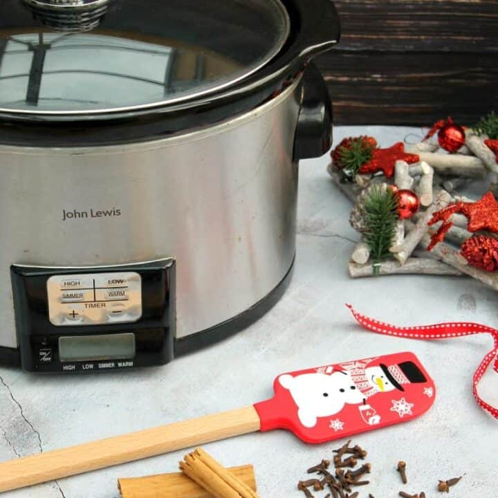 Slow cooker surrounded by Christmassy decorations.