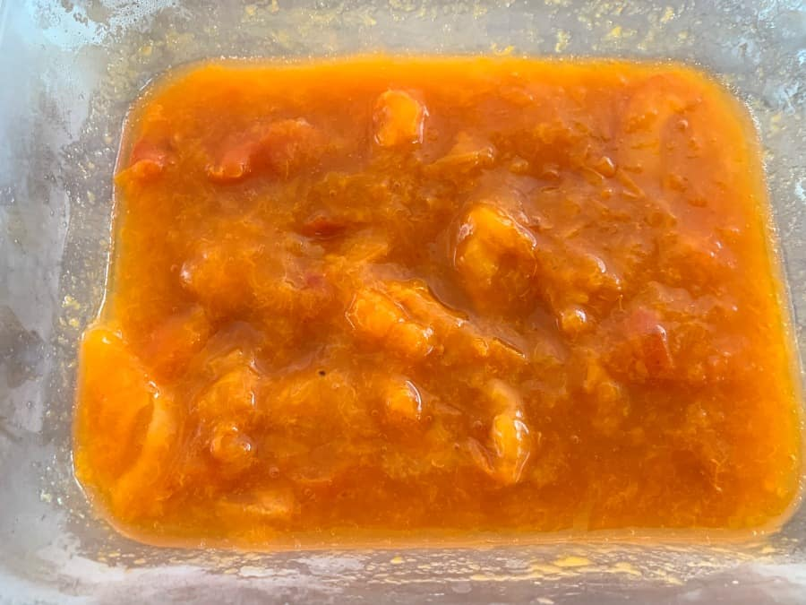 A tub of cooked apricots.