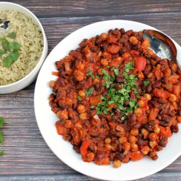 Serving bowl of bean chilli topped with coriander with a bowl of rice in next to it.