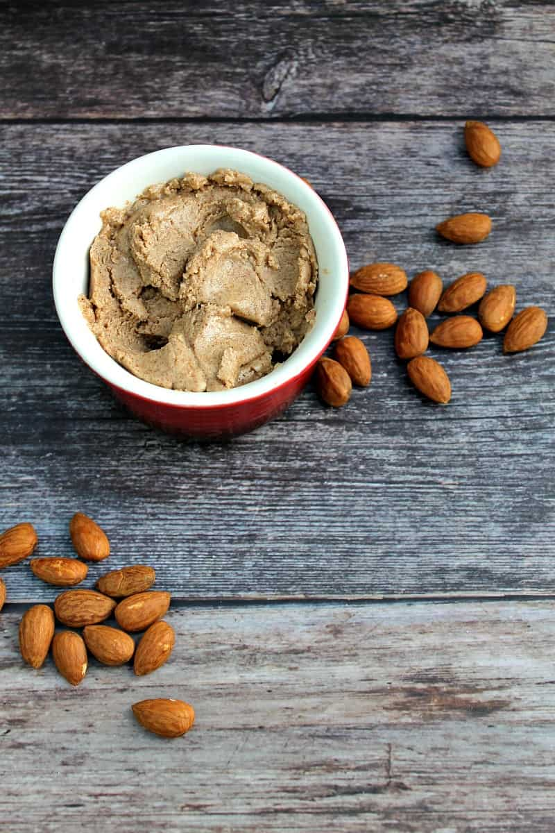 Almond butter in a small pot, with almonds around it.