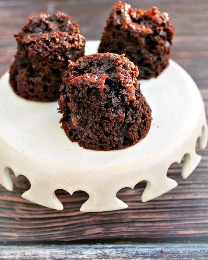 Little chocolate muffins on a small cream cake stand.