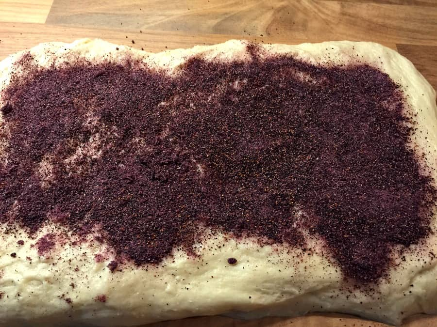 Covering the rolled out dough with blueberry powder.