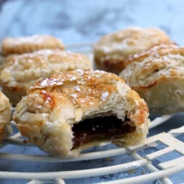 Close up of mince pies on a cooling rack, one with bite taken out of it.