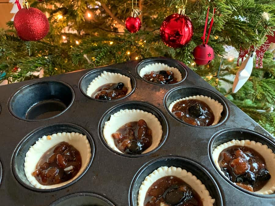 Mince pie bases filled with mincemeat with Christmas tree in background.