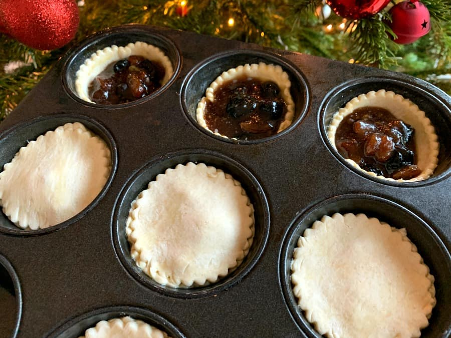 Putting lids on mince pies in the tin.
