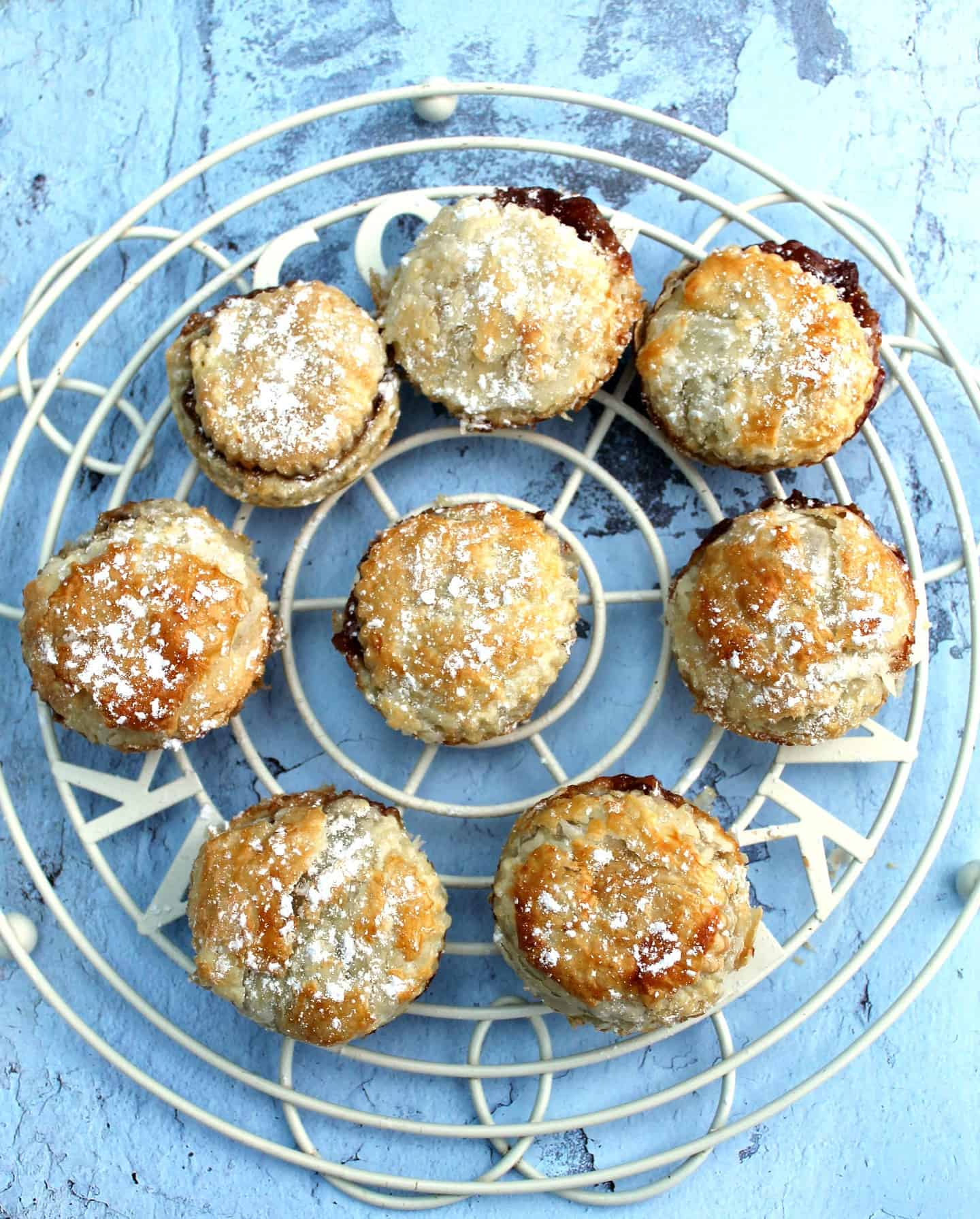 Mince pies on a white round cooling rack, on light blue background.