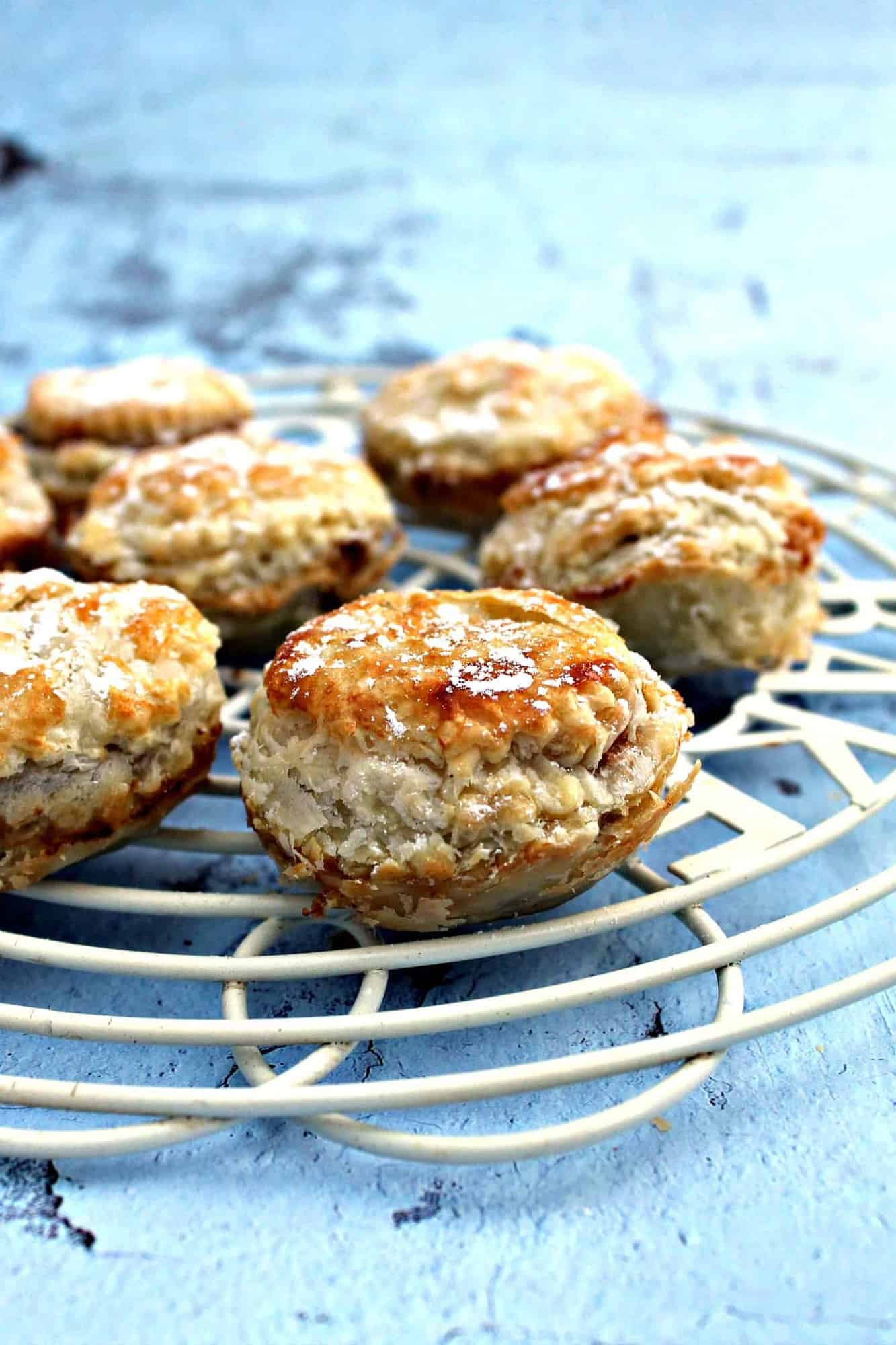 Mince pies on a rack on light blue background.