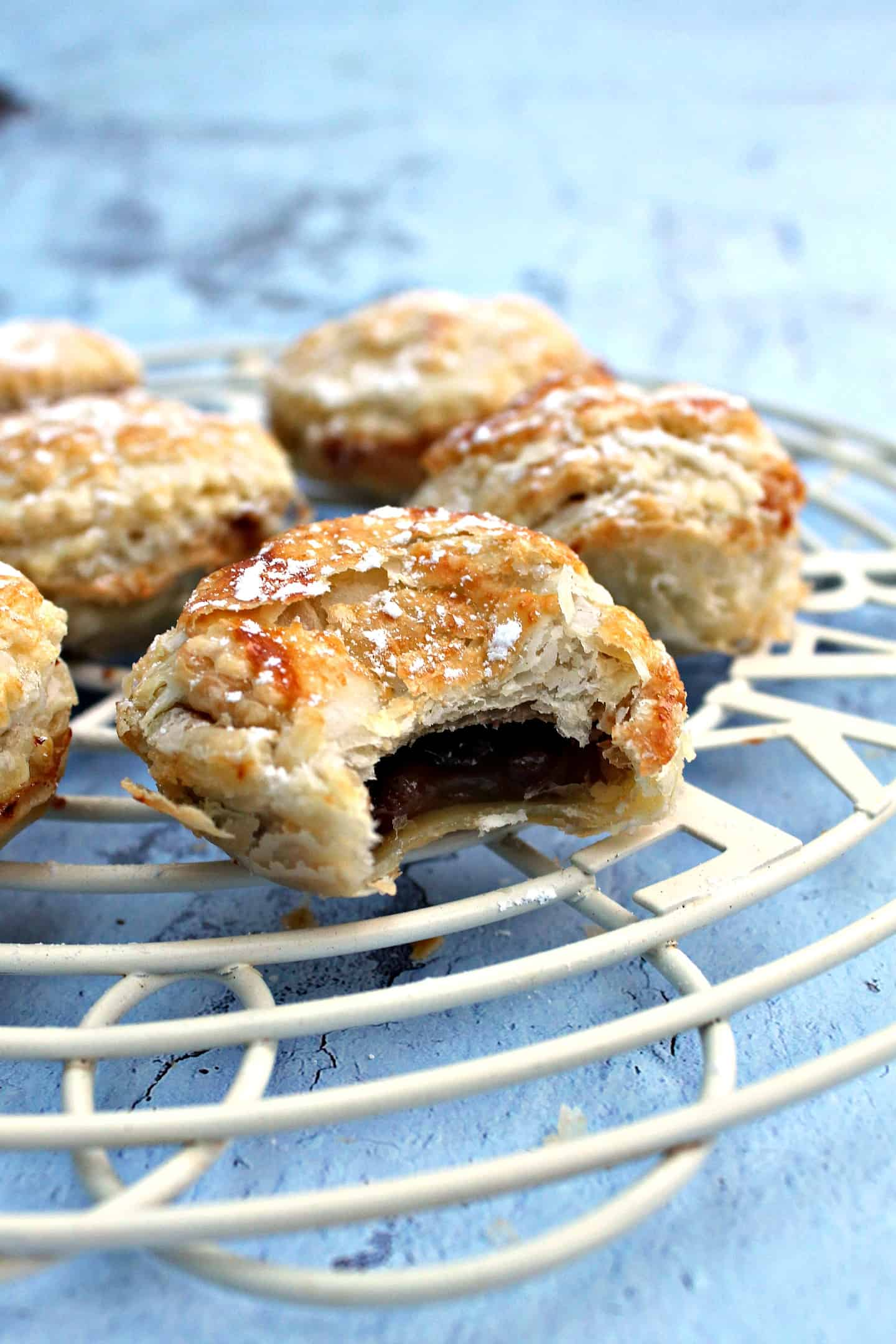 Mince pies on a white cooling rack on a blue background.
