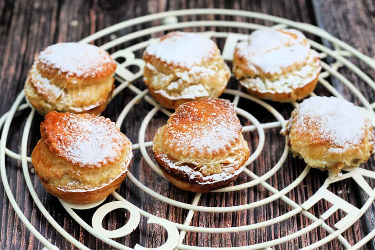 Mince pies made with puff pastry on a cooling rack.