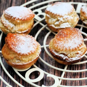 Close up of tall puff pastry mince pies with icing sugar on top.