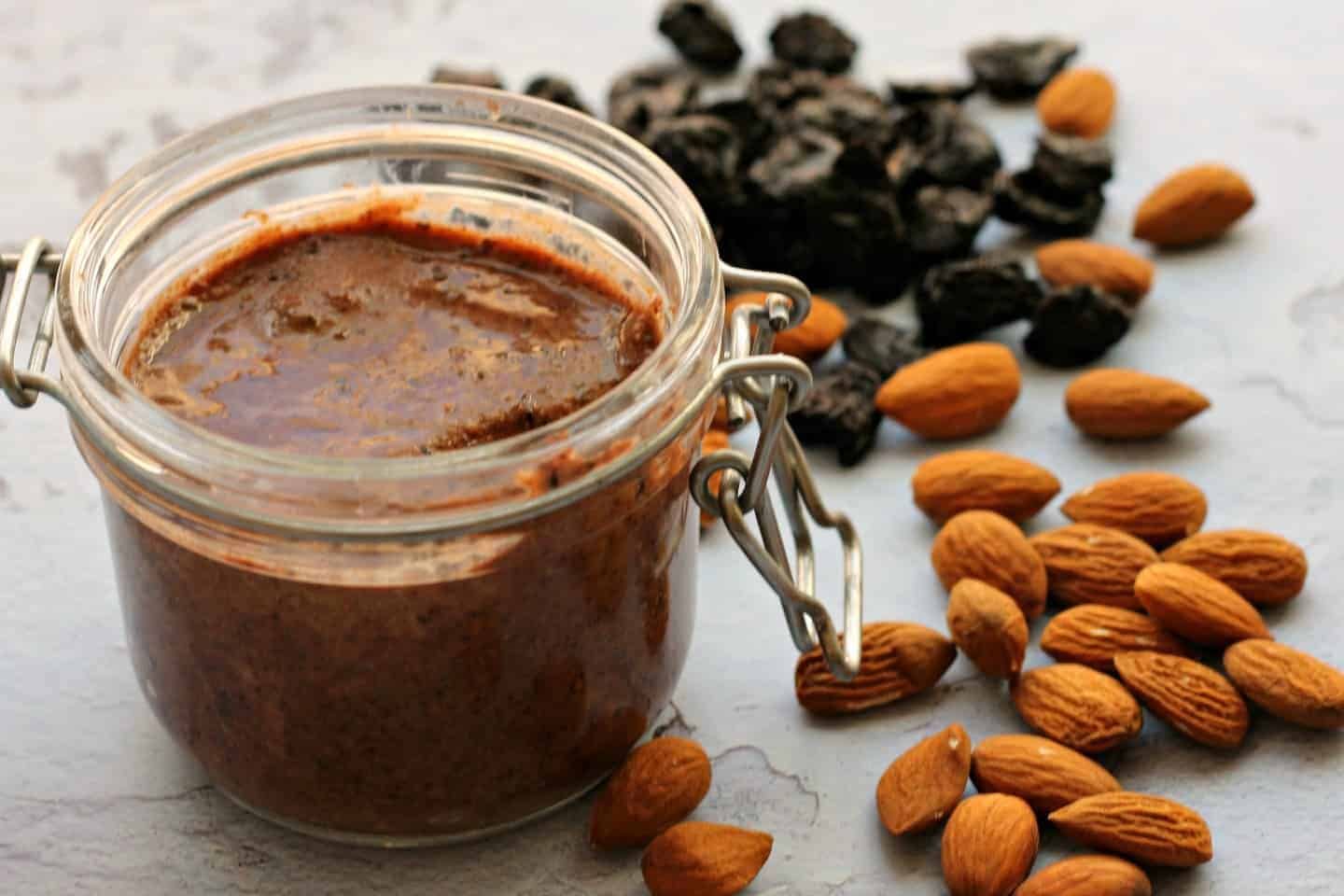 A pot of almond butter on a grey background with almonds and cherries around it.