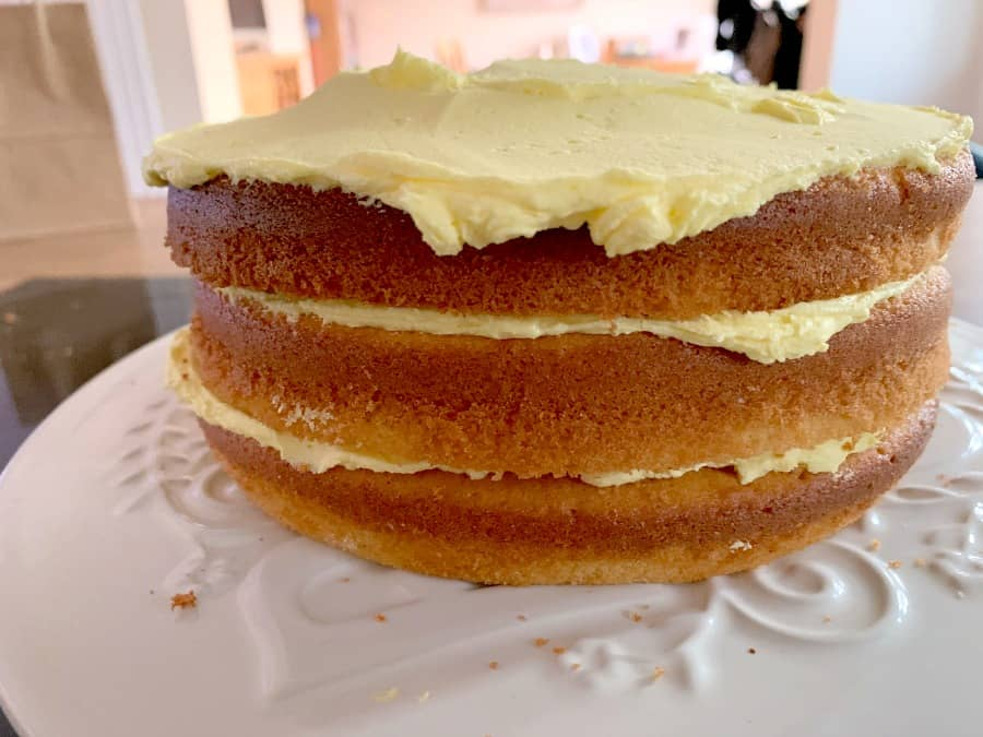 Three layers of cake with first layers of buttercream on top of each layer.