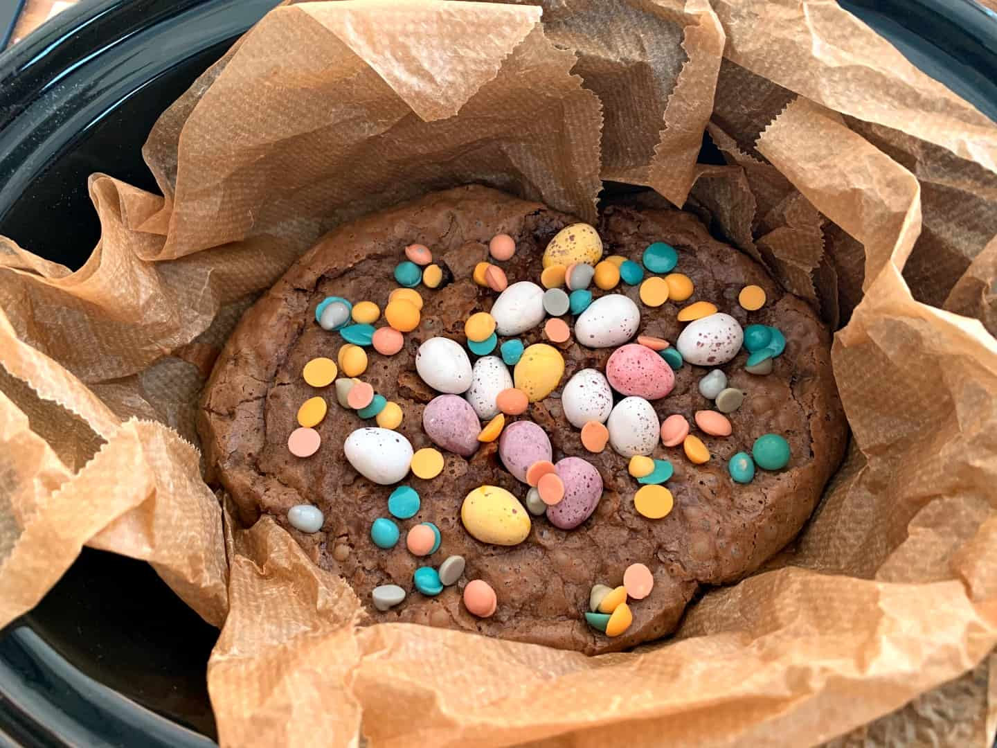 Brownies in slow cooker pot topped with pastel Mini Eggs.