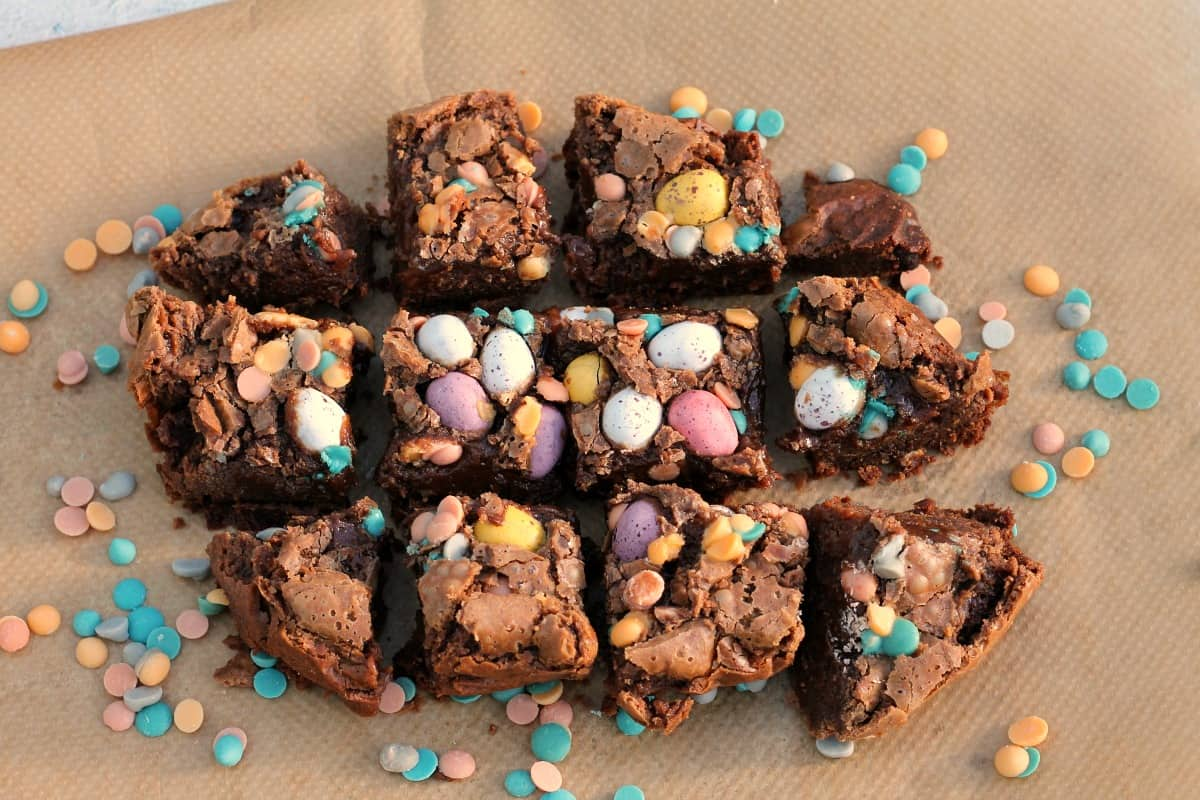 Squares of brownies with Mini eggs on top, on baking paper.
