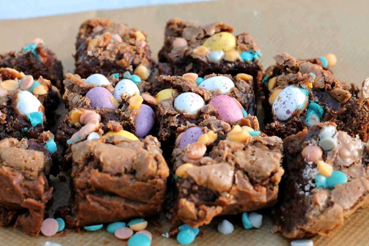 Close up of brownies with pastel chocolate eggs.