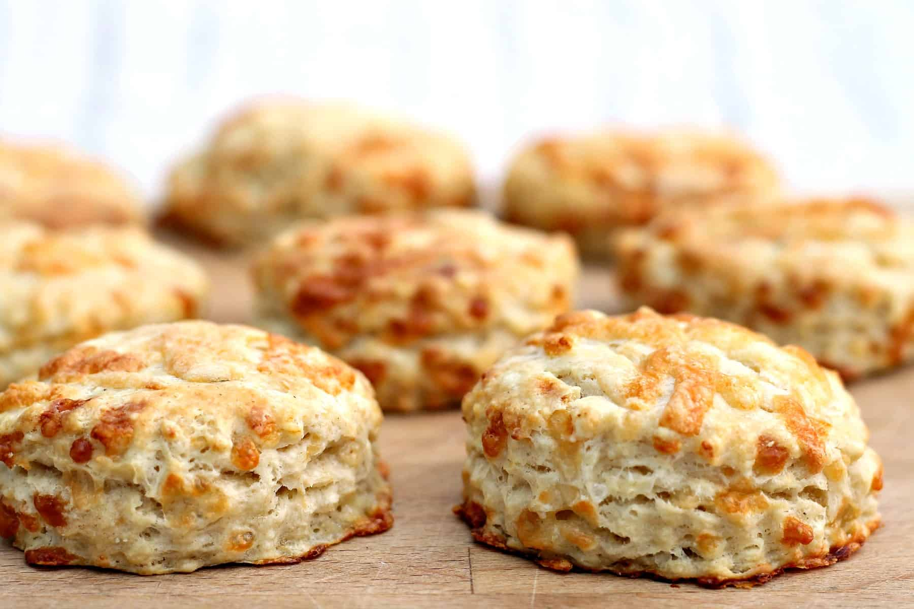 Close up of scones on a wooden board, from the side.