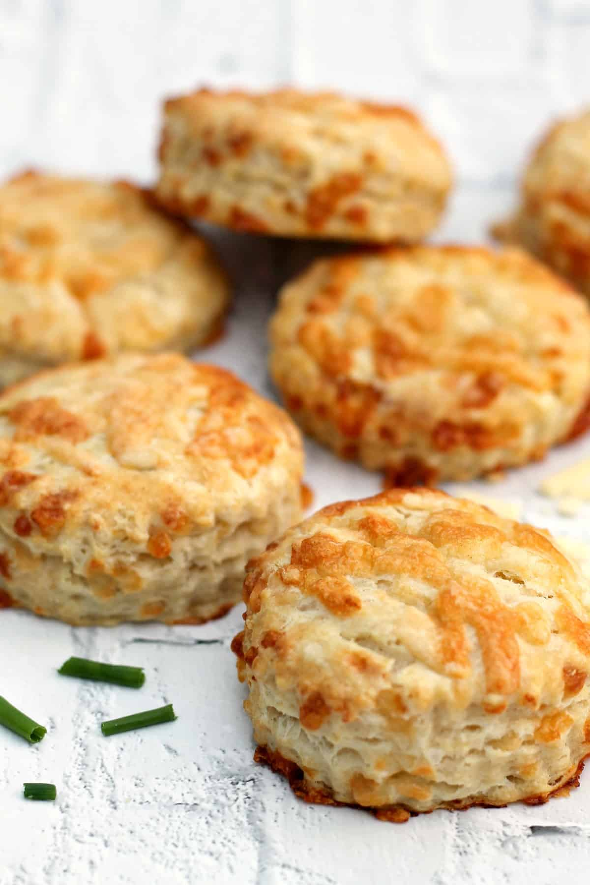 Close up of several cheese scones on white background, with snipped chives.