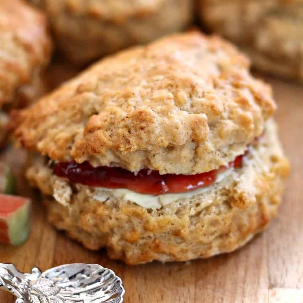 Close up of a scone filled with butter and jam.
