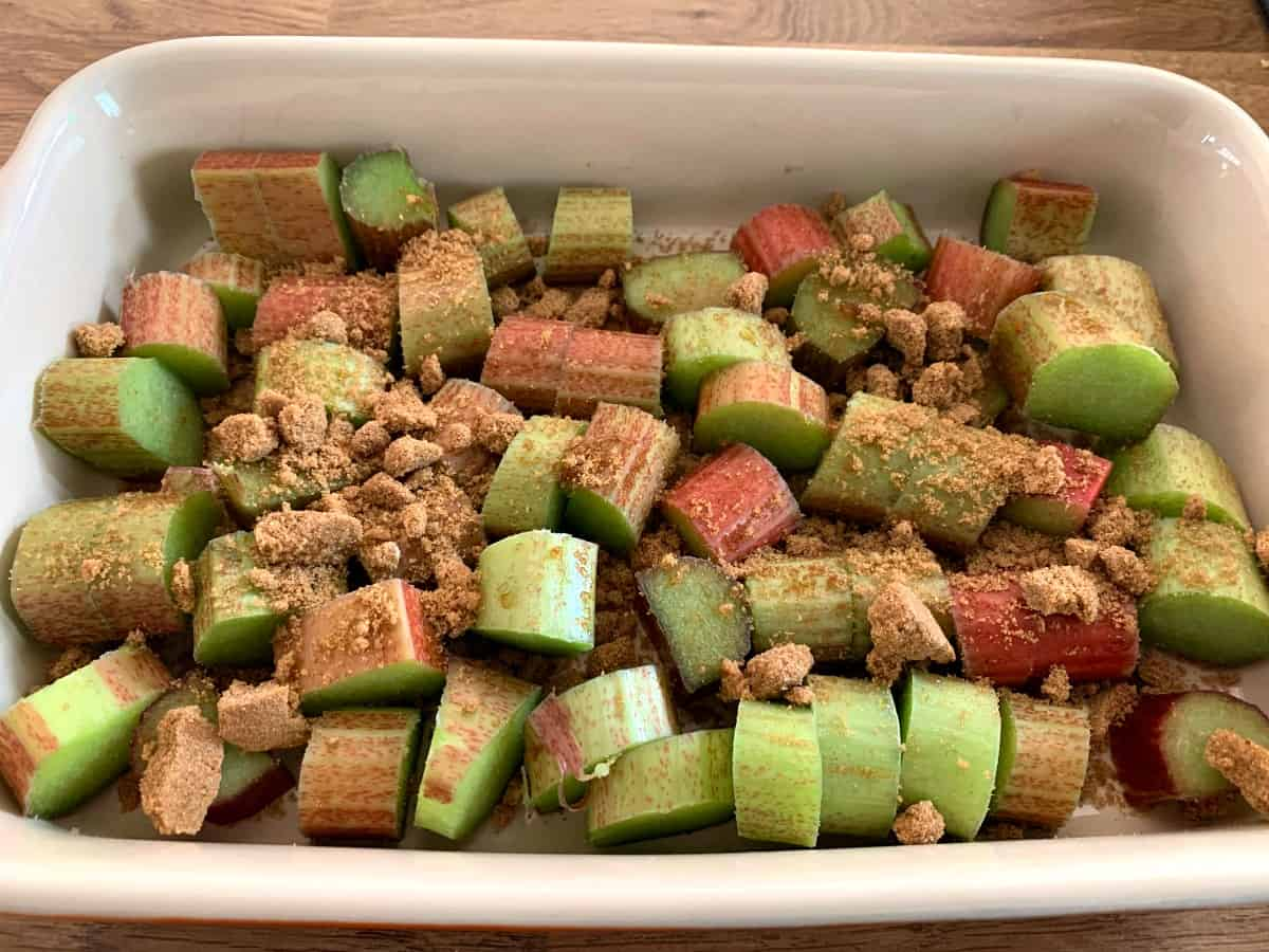 A dish of chopped rhubarb and brown sugar, ready to cook.