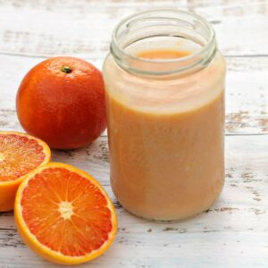 Jar of orange curd with oranges on a white wooden background.