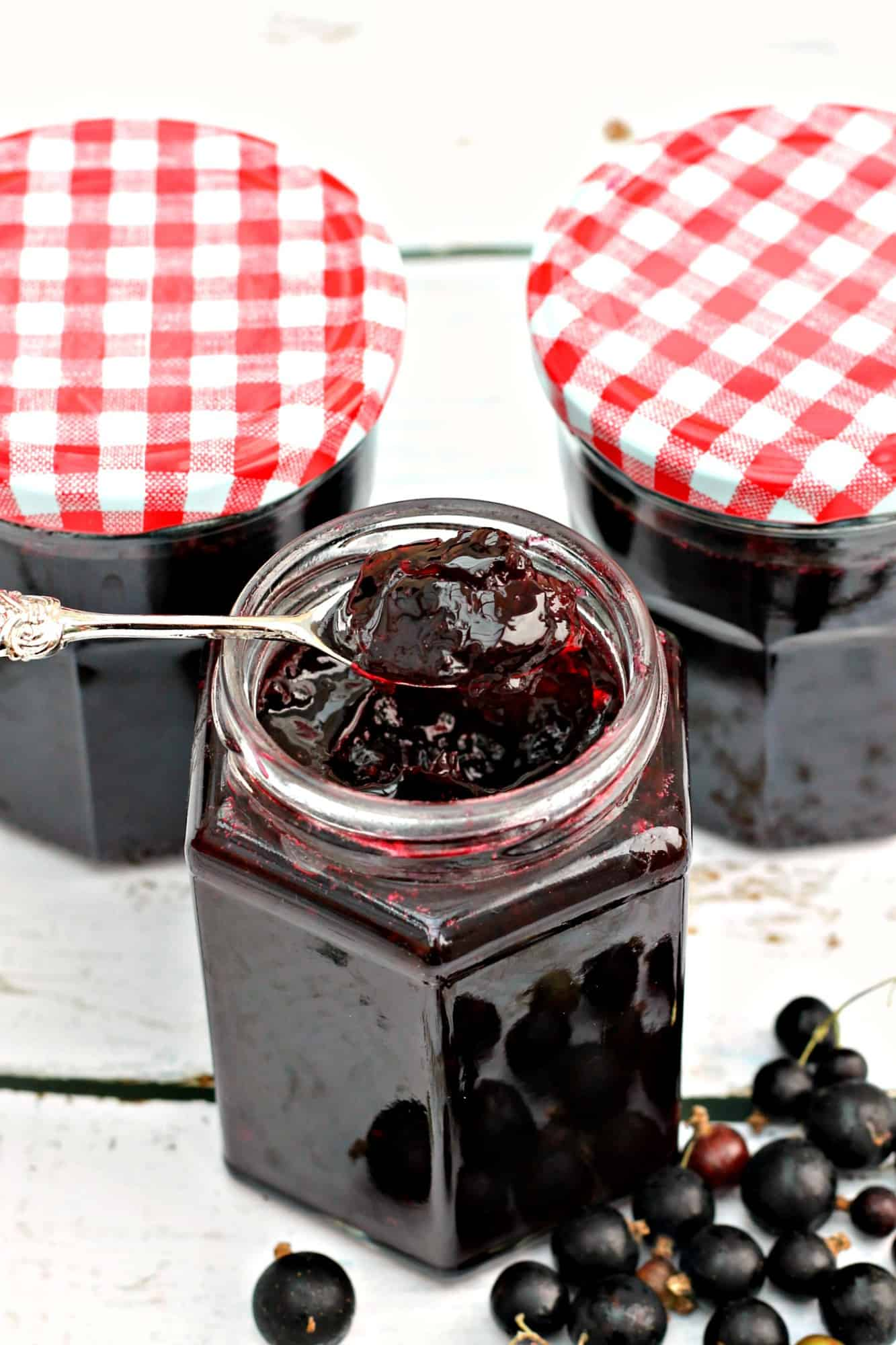 Jar of jam with a spoon of jam above, showing the perfect set.