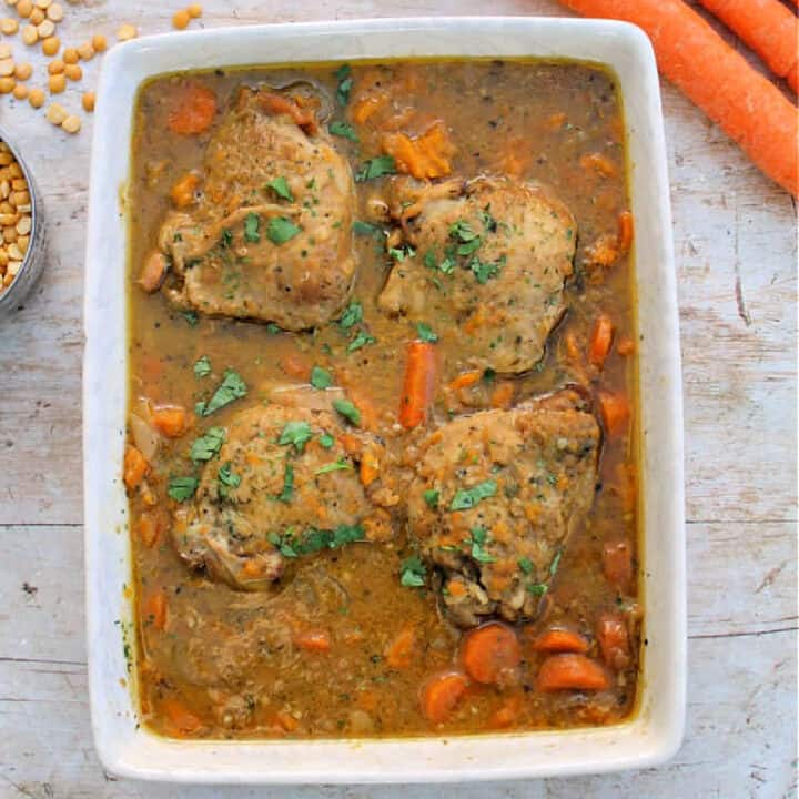 Chicken casserole in white serving dish, carrots and lentils in background.