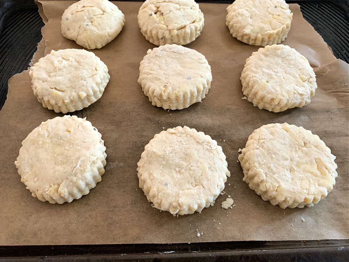 Cheese scones after cutting out on a baking tray lined with brown baking paper.
