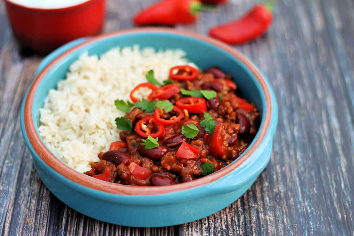 Close up of light blue bowl with chilli and rice, with red chillis in background.
