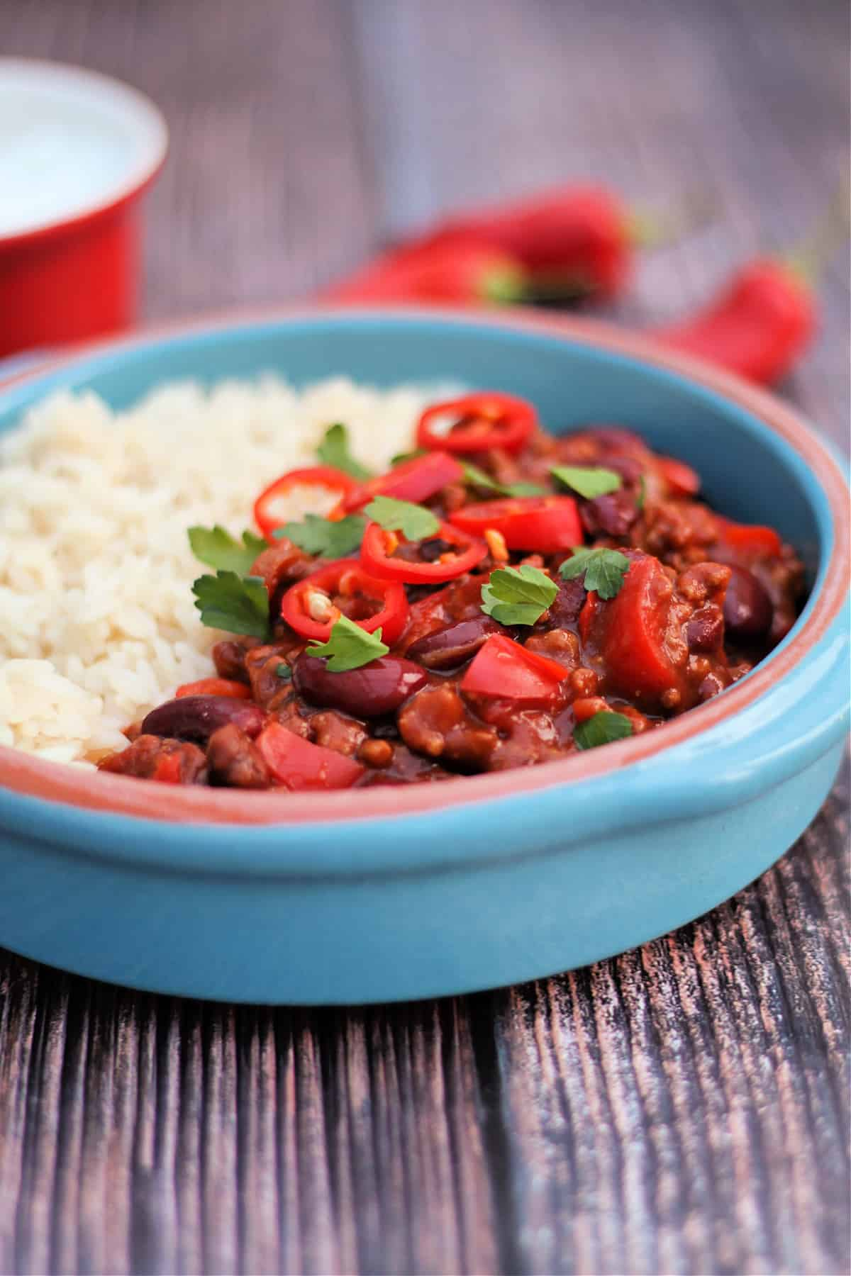 Close up of blue earthenware bowl with chilli con carne topped with sliced red chilis and flat leaf parsley.