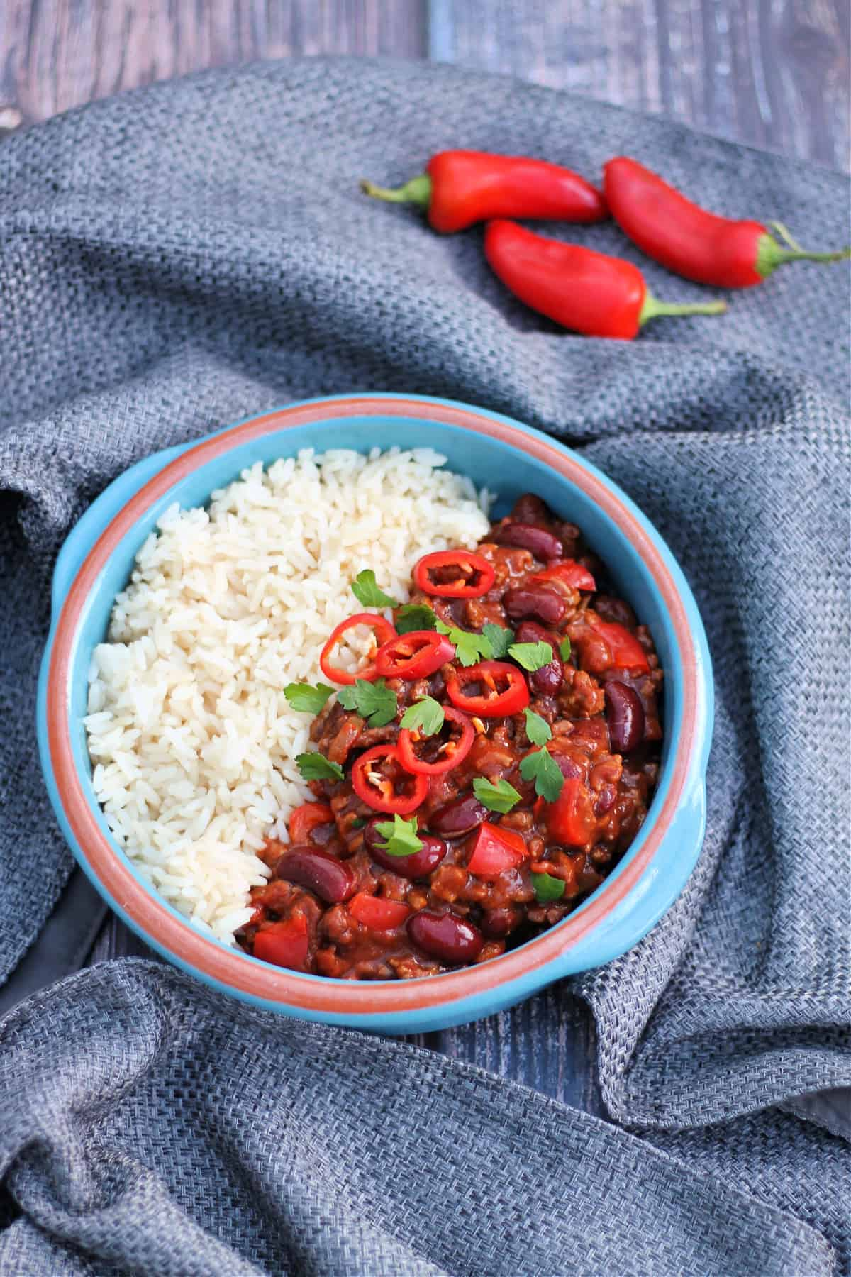 Bowl of chilli and rice with red chillis and herbs on top, on grey fabric background.