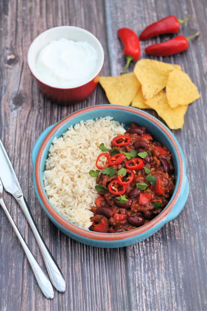 Bowl of chilli and rice with tortilla chips, sour cream and chillis.