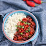 "Overhead view of bowl of chilli and rice on grey fabric, with text overlay ""crockpot chilli""."
