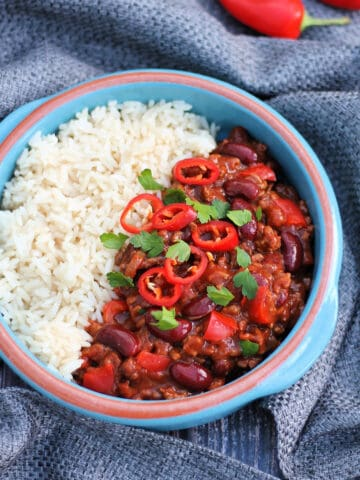 Overhead view of bowl of chilli and rice on grey fabric.