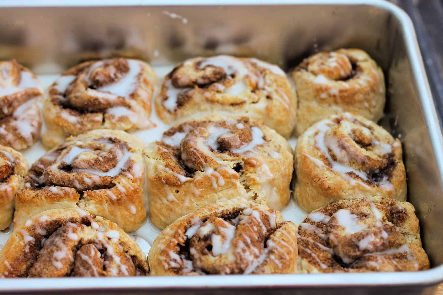 Cinnamon rolls with icing in baking tin.