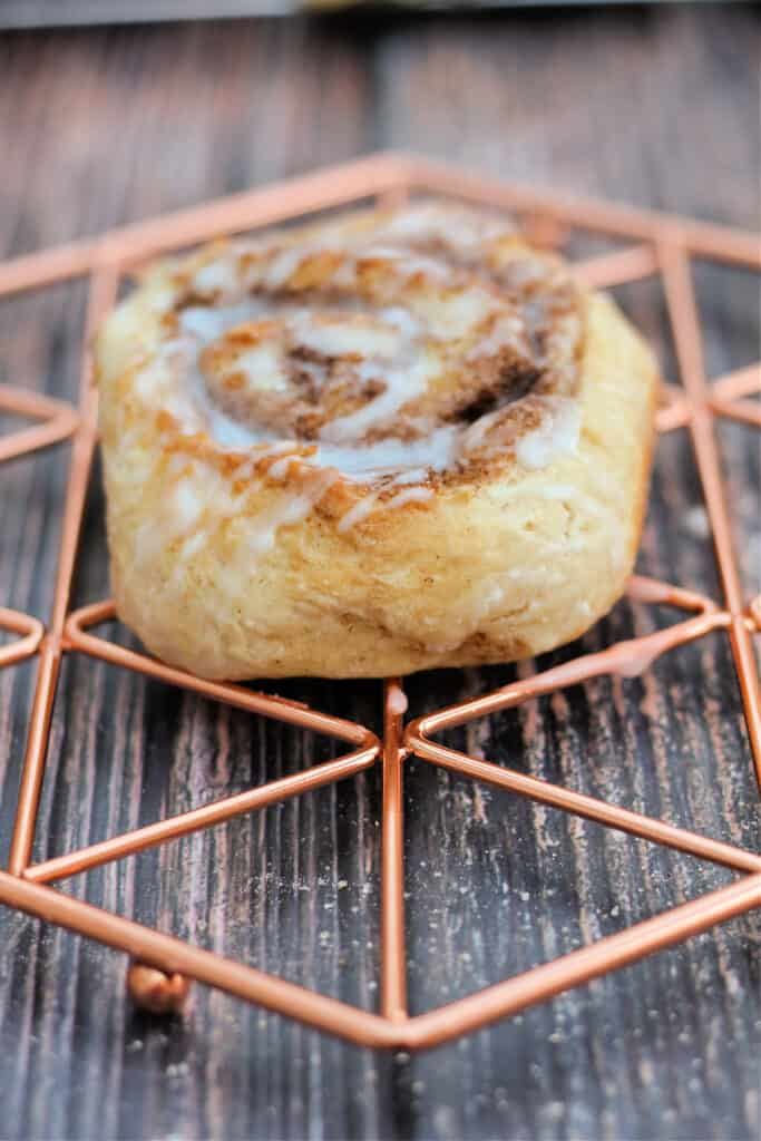 A single cinnamon roll on a copper cooling rack.