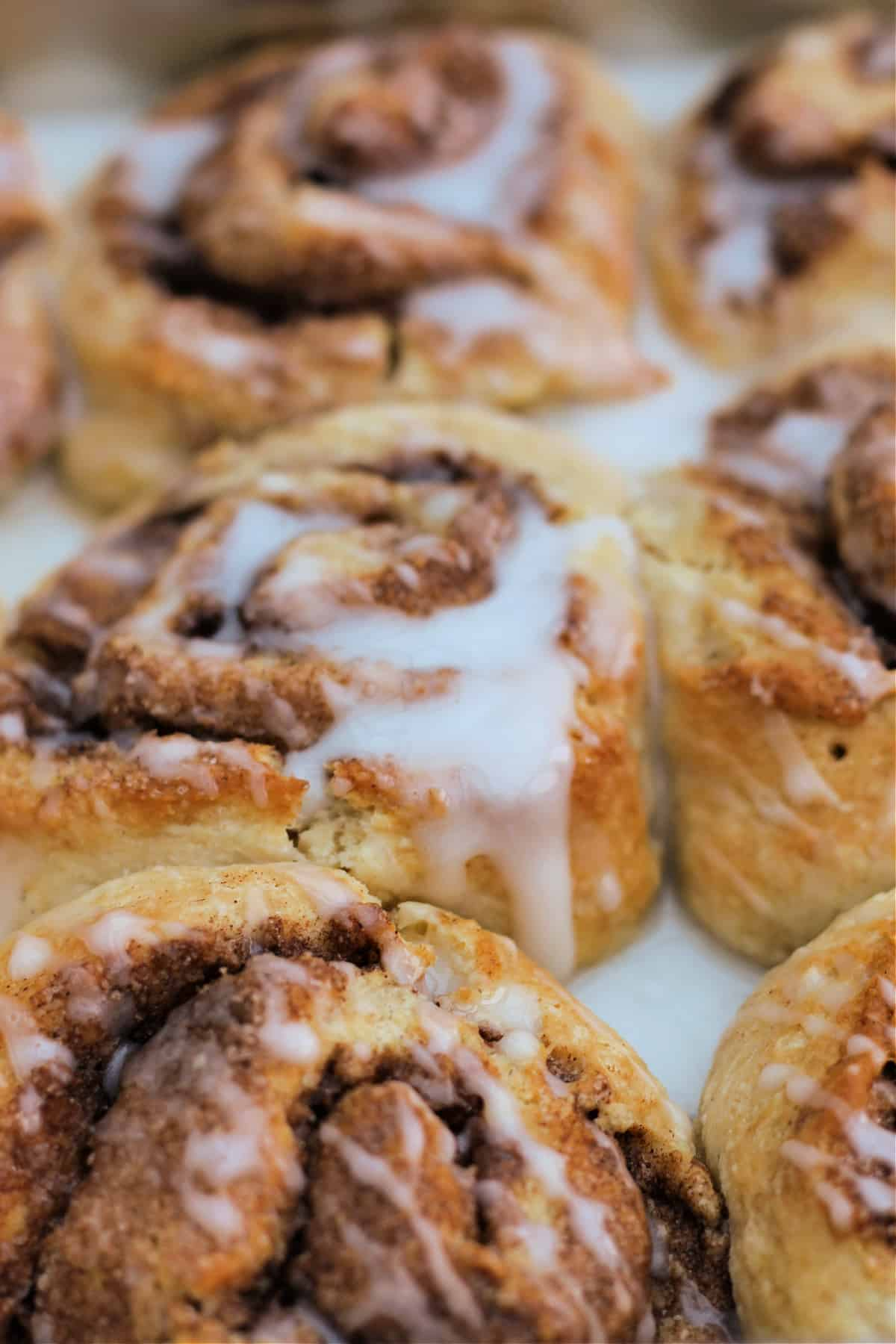 Close up of cinnamon rolls with icing drizzles.