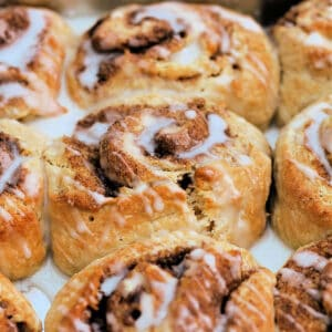 Close up of cinnamon swirls with icing drizzled over in baking tin.
