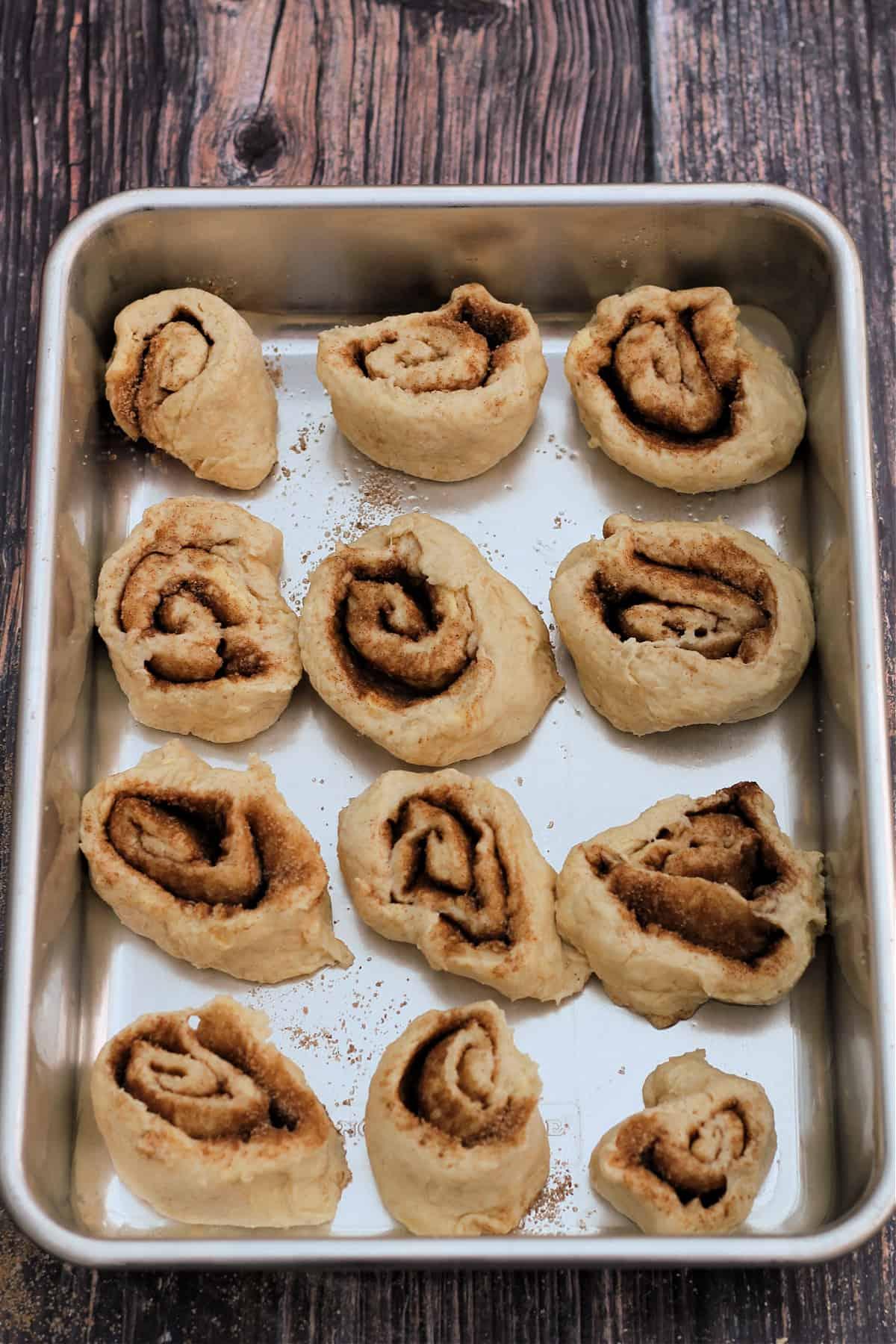 Cinnamon swirls before baking, in baking tin.