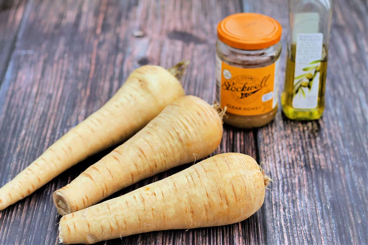 Some parsnips, a jar of honey and a bottle of oil on a wooden surface.