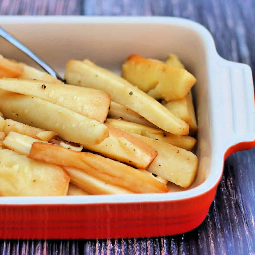 Slow cooker roast parsnips in red serving dish.