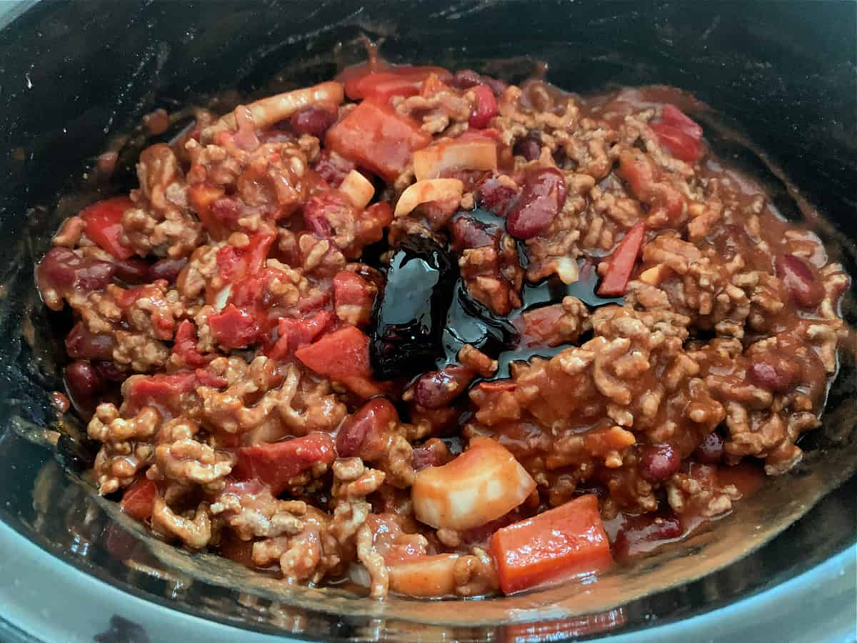 Chilli ingredients mixed in slow cooker pot, ready to cook.