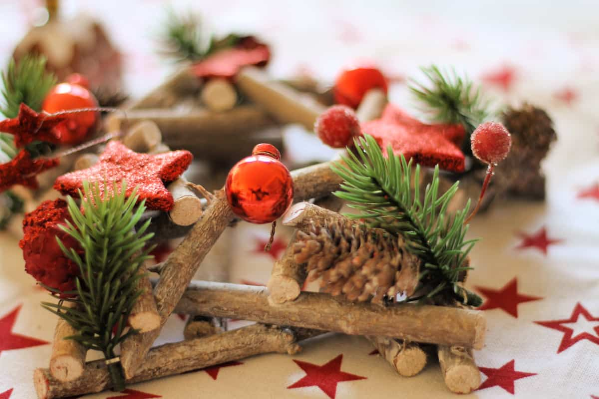A festive wooden decoration with pine cones, red baubles and stars, on a table.