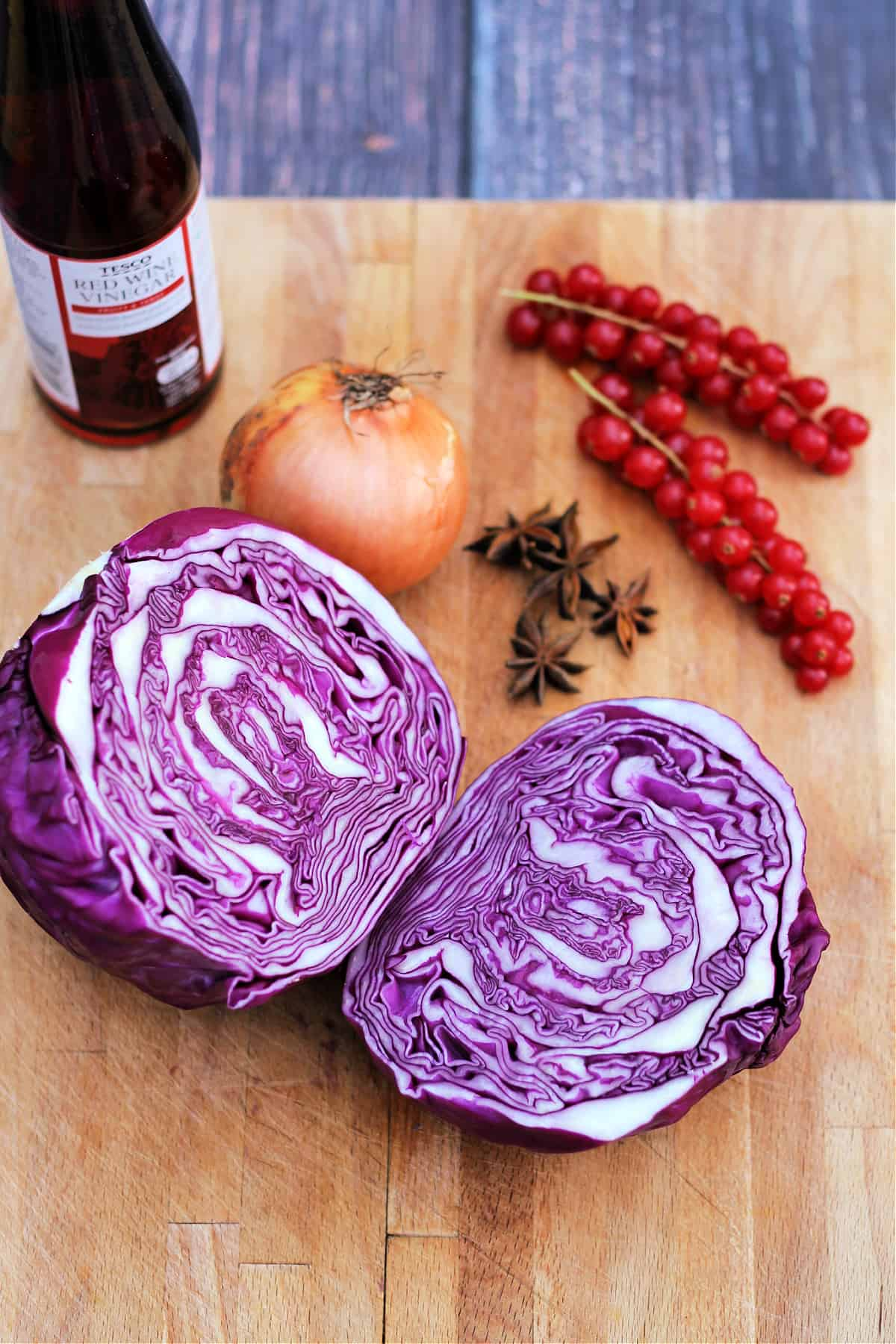 A halved red cabbage, onion, star anise and bottle of red wine vinegar on a board.